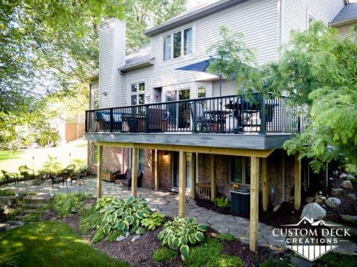 2nd story grey composite deck with unique and beautiful landscaping under the deck