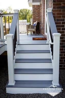 Grey and white stairs leading from backyard to a deck on the back of a new construction home