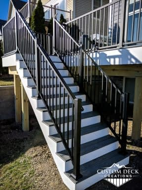 Grey and white stairs with black railing leading up to a 2nd story composite deck