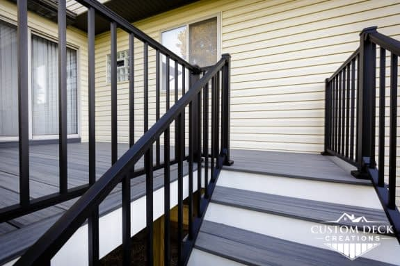 Grey and white backyard deck and stairs with black aluminum railing