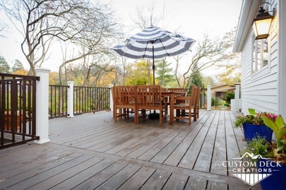 Backyard deck, brown, with railing, posts, table, chairs and umbrella