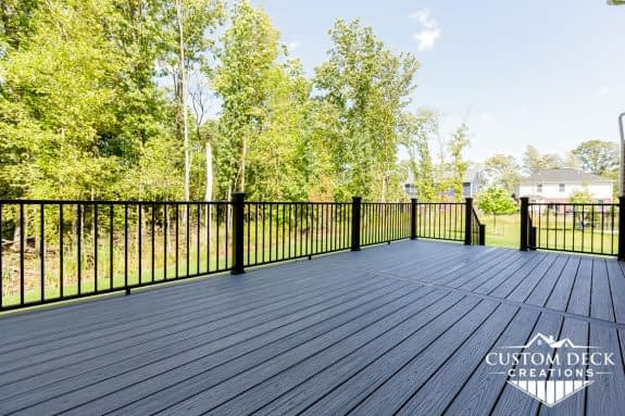 Backyard deck in grey boards and black railing built by Custom Deck Creations