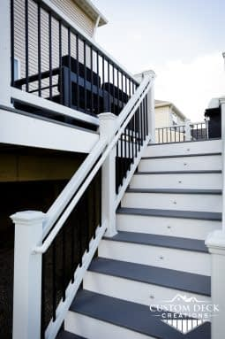 Grey and white stairs with riser lights leading up to a grey 2nd story composite Trex deck in New Hudson Michigan