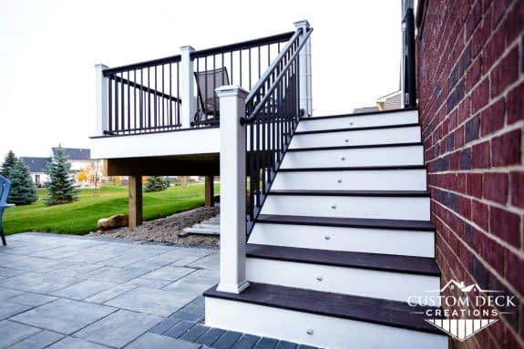 Stairs with small riser lights leading from a paver patio to a composite deck on the back of a home