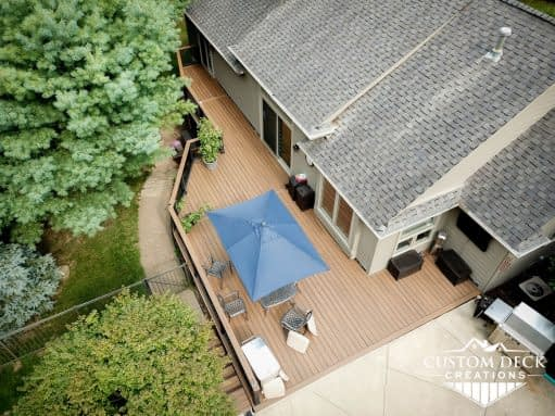 Aerial view of a backyard composite Trex deck with drink rail