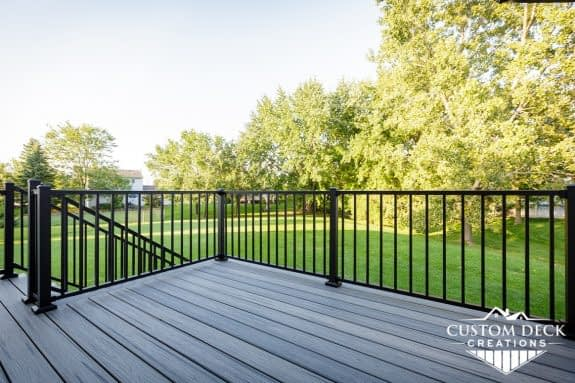 View of open green backyard on top of a grey and black composite backyard deck