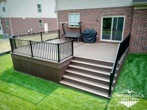 Composite deck with stairs and railing leading to backyard