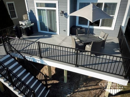 Aerial view of a backyard deck with patio furniture and grill