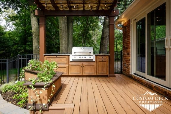Outdoor kitchen with granite and built in grill with pergola and lights above it
