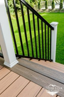 Stairs on an outdoor Trex composite deck with black and white railing with railing post cap lights