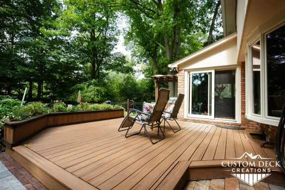 Outdoor backyard deck low to the grade shown with an outside shower and paver patio