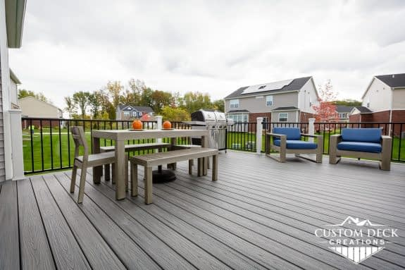 Grey deck with patio furniture and grill in the back of a new construction home