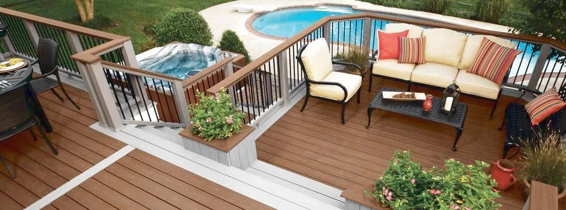 Brown composite deck with furniture and backyard pool